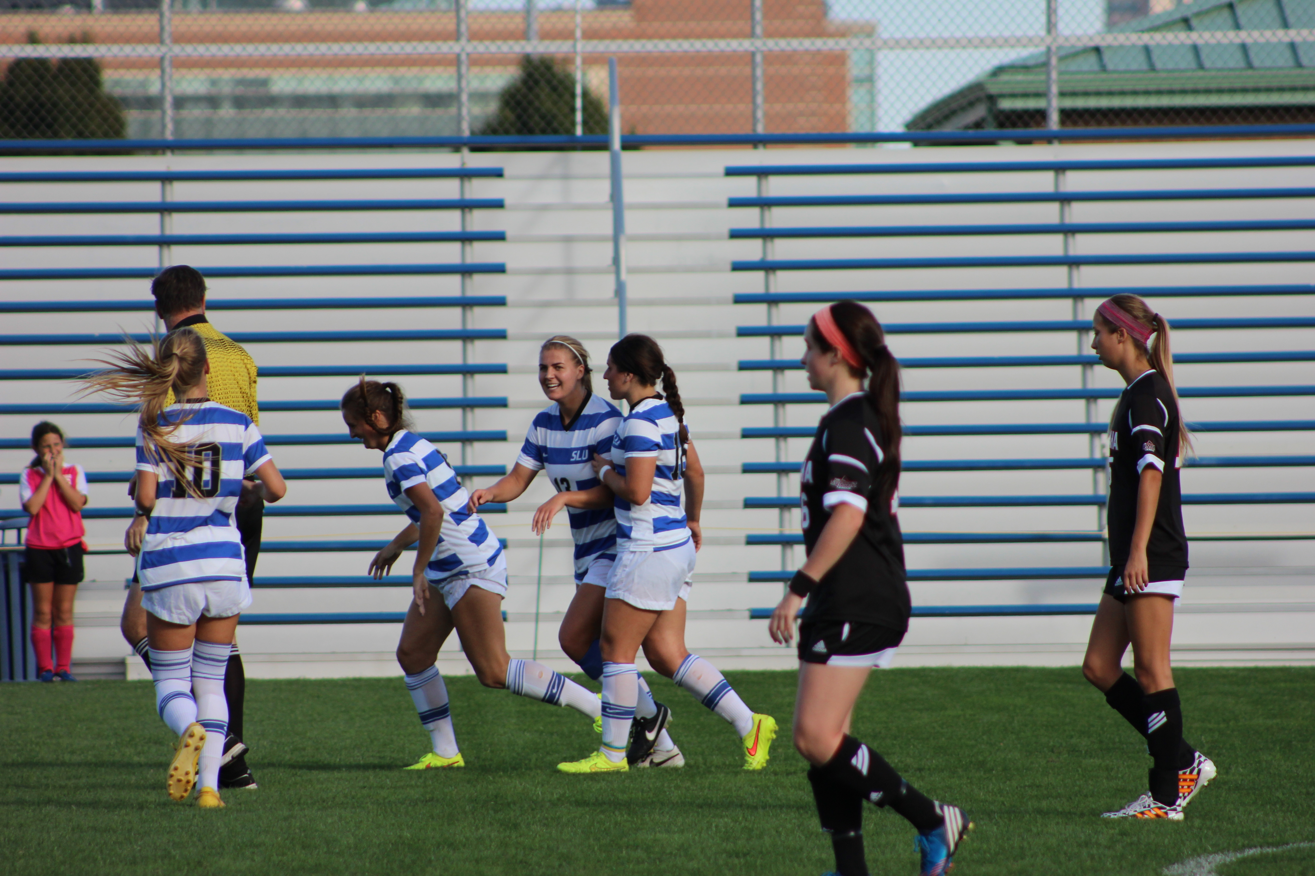 Celebrate: The women's soccer team celebrates one of four goals in a game against UNO. The Billikens scored two goals in each half of the contest. Emma Kelly / Staff Photographer